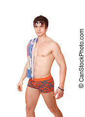 Muscular male model in swimwear over white background