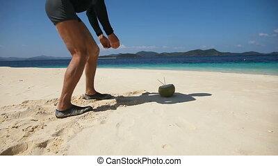 Man on the beach drinking coconut juice - Man in sunglasses...