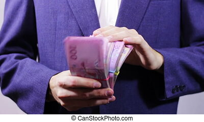 Businessman with Wads of Money in Hands - Businessman counts...