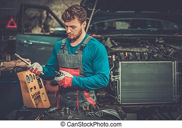 Mechanic with pneumatic tool in a workshop
