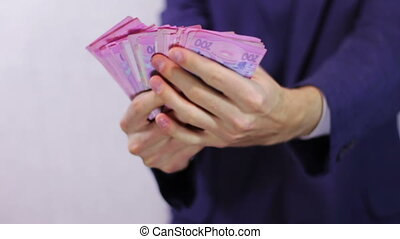 Businessman Counts Money in Hands - Businessman counts tens...