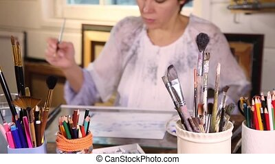 Out of focus painter - Middle age woman painting with...