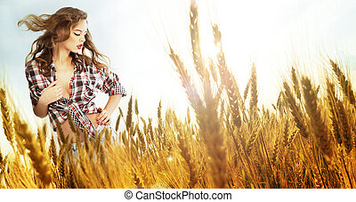 Woman standing in a wheat field; sunny summer day, lens...