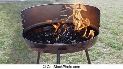 Blazing fire in a portable barbecue during the prpearation...