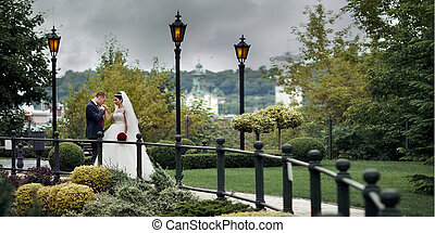 Romantic newlywed couple, groom kissing bride hand in european park with a town in the background