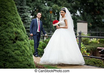 Newlywed valentynes posing in a romantic european park with roses bouquet
