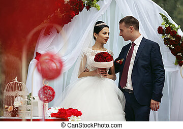 Happy newlywed romantic couple at wedding aisle with red decorations and flowers