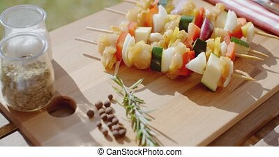 Four chicken and vegetable kabobs on cutting board - Four...