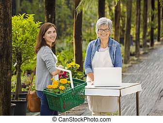 Worker and customer in a green house