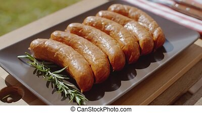Smoked sausages and rosemary lying in a platter ready for...