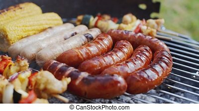 Sausages and vegetables cooking on grill - Various large...