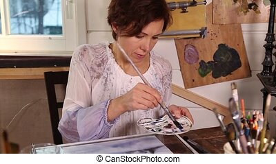 Woman artist drawing picture in stu - Caucasian woman artist...