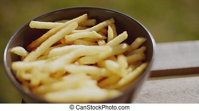 Bowl of freshly fried potato chips on a wooden slatted...
