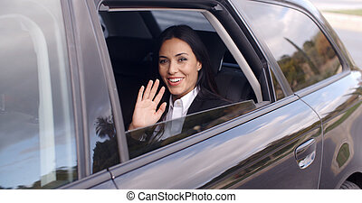 Cute business woman sitting in car waving hand - Exterior...