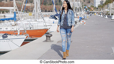 Pretty woman strolling on a waterfront promenade -...