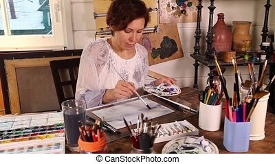 Artist working in the studio - Middle age woman painting...