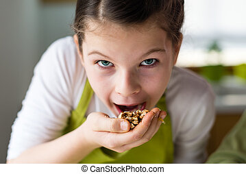 Funny Girl eating walnuts - Healthy eating, young girl...