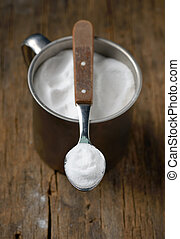 Spoonful of sodium bicarbonate on old wood table