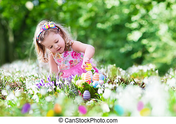 Little girl on Easter egg hunt - Little girl having fun on...