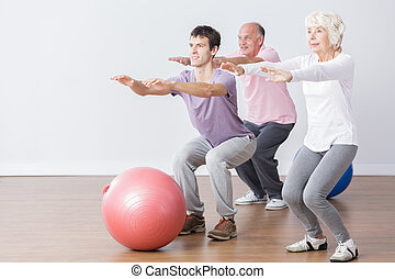 Seniors doing squats during classes with physiotherapist