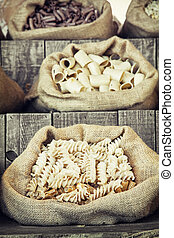 Various pasta in canvas bags on the wooden retro board