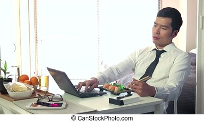 Hungry Busy Man Eating Sushi Food - Asian people working at...