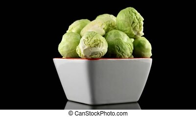 Fresh brussels sprouts on white ceramic bowl isolated on...