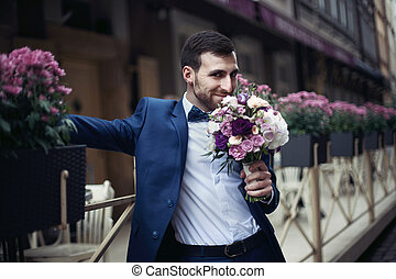 Happy smiling handsome bearded groom in blue suit holding a...