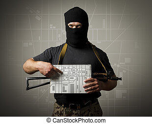 Gunman and city map. - Man in mask with gun is holding a...