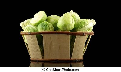 Fresh brussels sprouts on wooden basket isolated on black...