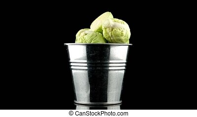Fresh brussels sprouts on metal tin isolated on black...