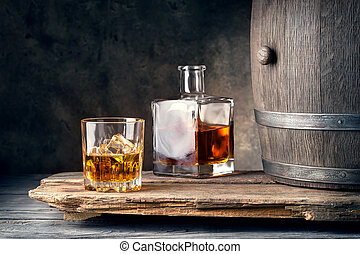 Glass of whiskey with ice decanter and barrel on wooden...