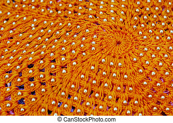 golden beads on orange cloth - fabric design with golden...