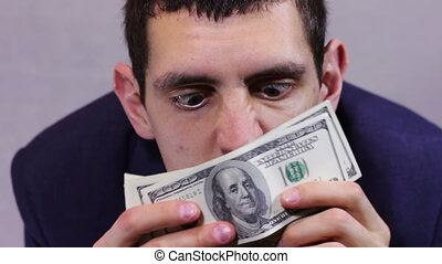 Businessman Sniffing Money. - Businessman counts several...