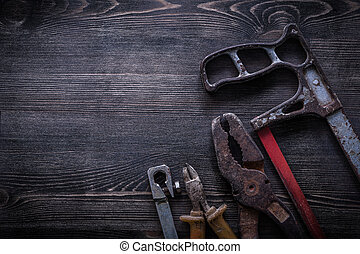Rusty hacksaw nippers pliers on wooden board construction...