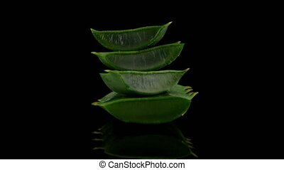 Sliced aloe leaf and water drops isolated on black...