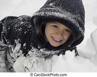 small child playing in the snow. - a young boy child wearing...