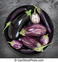 Eggplant Varieties in Black Bowl on Slate Overhead View