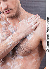 Attractive fit guy is taking a shower - Handsome young man...