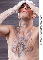 Cheerful young guy is washing skin with soap - I like taking...
