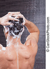 Handsome fit guy is cleaning his head - Cheerful young man...