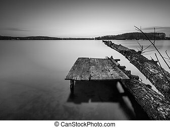 Black and white lake landscape with small wooden pier -...