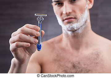 Attractive young man is presenting new shaver - This razor...