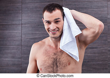 Handsome fit guy is drying himself after bathing - Purity is...