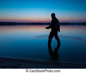 Man standing in lake water at sunset - Man in lake water at...
