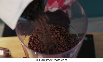 coffee beans in a coffee grinder - coffee beans are poured...