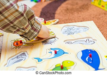 Little child puts the simple puzzle on the floor Playing on...