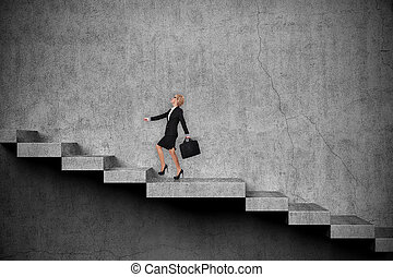 Success concept - Businesswoman with briefcase climbs the...