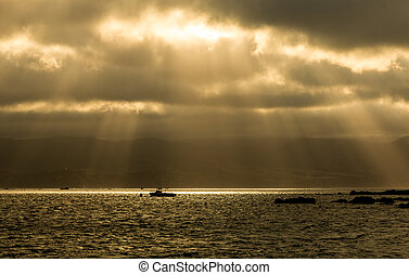 Sun Rays Boat - Small boat in a bay with sun rays beaming...