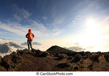 young woman backpacker hiking to beautiful mountain peak